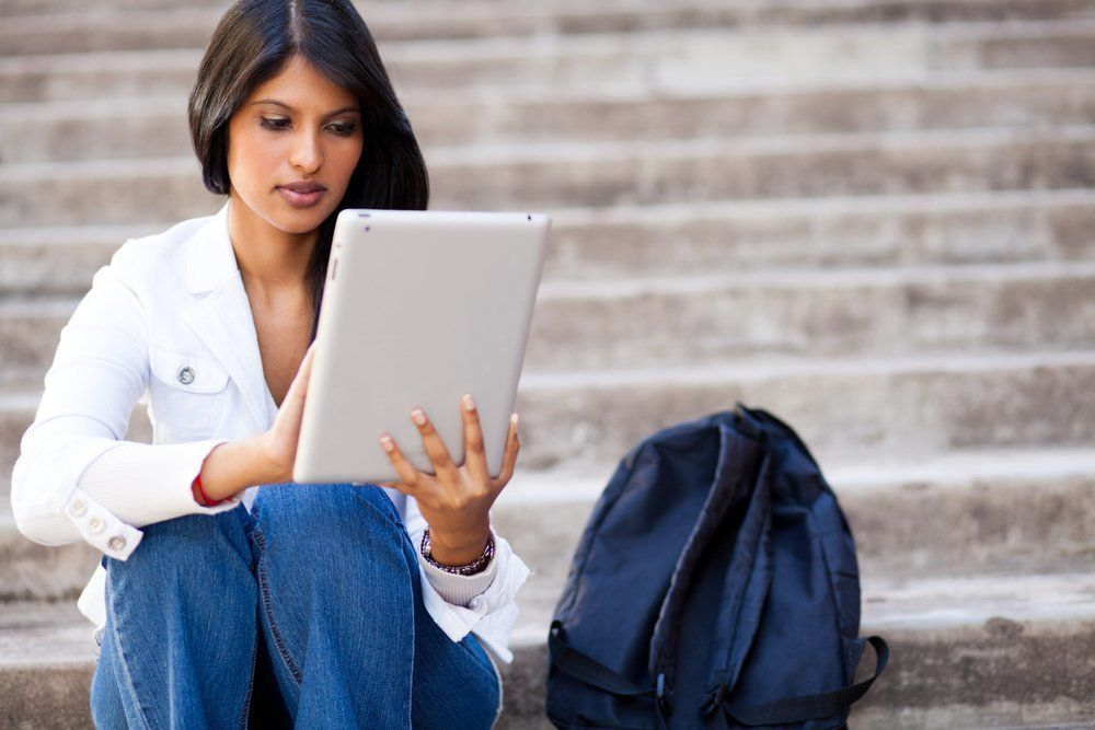 young female college student using tablet computer outdoors